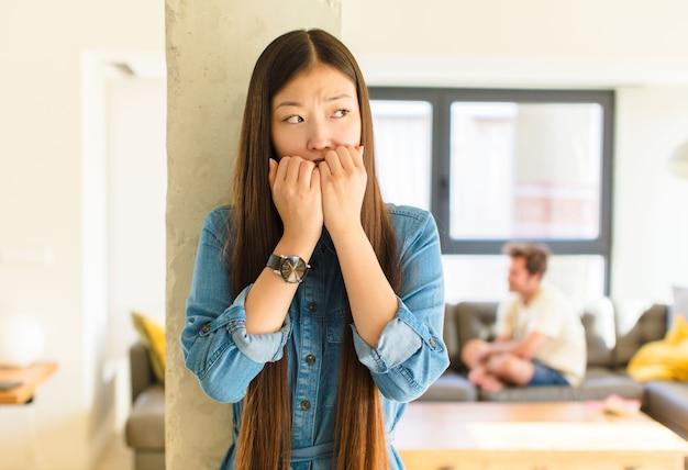 Jovem, linda mulher asiática, parecendo preocupada, ansiosa, estressada e com medo, roendo as unhas e olhando para o espaço lateral da cópia