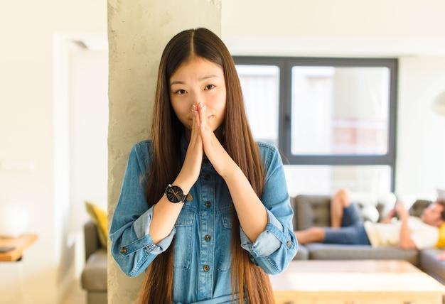 Jovem, linda mulher asiática, preocupada, esperançosa e religiosa, orando fielmente com as palmas das mãos pressionadas, implorando perdão