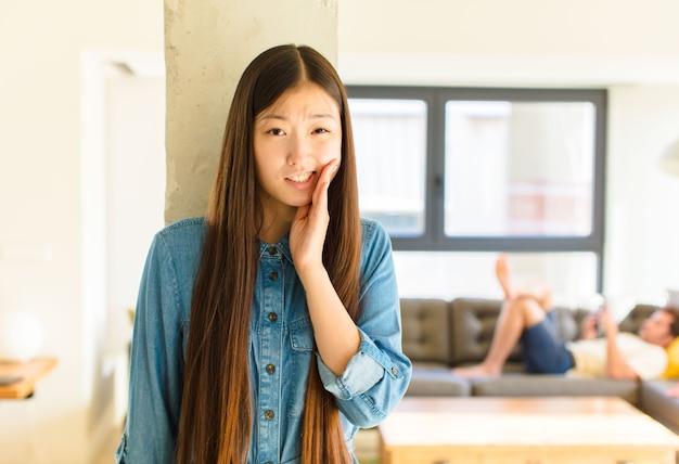 Jovem, linda mulher asiática, segurando a bochecha e sofrendo de uma dor de dente dolorosa, sentindo-se doente, infeliz e miserável, procurando um dentista