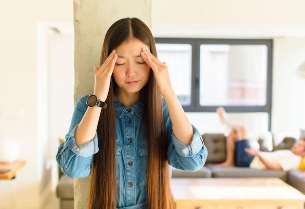 Jovem, linda mulher asiática vestindo uma camiseta dentro de casa