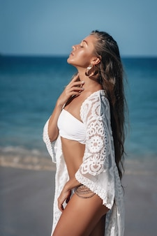 Jovem, linda mulher caucasiana da moda vestindo maiô branco e capa de praia de renda branca