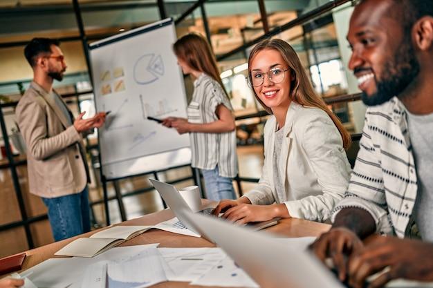 Jovem linda mulher caucasiana de óculos se senta com um laptop em uma mesa junto com seus colegas em um escritório moderno.