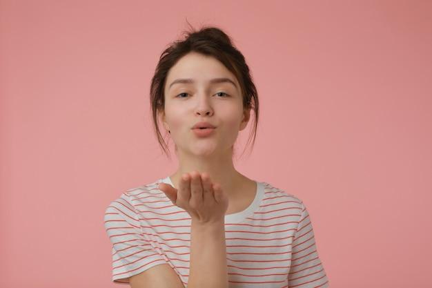 Jovem, linda mulher com cabelo castanho e coque. vestindo t-shirt com tiras vermelhas e mandando um beijo. conceito emocional. isolado sobre parede rosa pastel