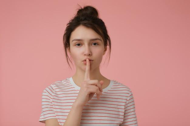 Jovem, linda mulher com cabelo castanho e coque. vestindo t-shirt com tiras vermelhas e mostrando sinal de silêncio. conceito emocional. isolado sobre parede rosa pastel
