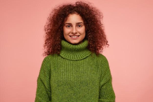 Jovem, linda mulher com cabelos cacheados ruivos. vestindo suéter verde de gola alta e com um sorriso lindo e brilhante, confiante. isolado sobre parede rosa pastel