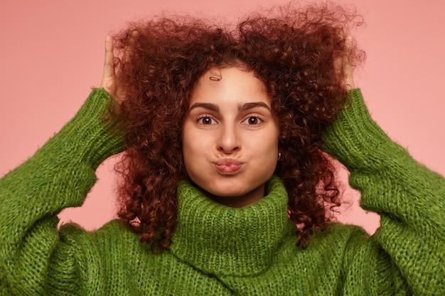 Jovem, linda mulher com cabelos cacheados ruivos. vestindo um suéter verde de gola alta e tocando seu cabelo, inflou as bochechas. isolado, close up sobre parede rosa pastel