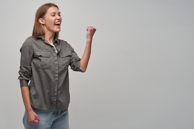 Jovem, linda mulher com cabelos castanhos compridos. vestindo jeans e camisa cinza. mantenha o punho levantado, virado e olhando para a direita no espaço da cópia, mostrando sua empolgação, isolado sobre um fundo cinza