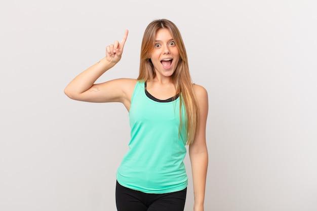 Jovem, linda mulher de fitness se sentindo um gênio feliz e animado depois de realizar uma ideia