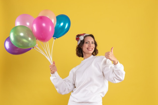 Jovem, linda mulher, de frente, segurando balões coloridos na cor amarela, emoção de ano novo de natal