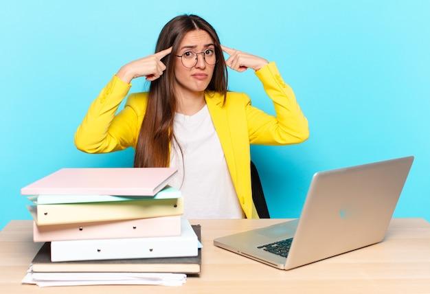 Jovem, linda, mulher de negócios com um olhar sério e concentrado, fazendo um brainstorming e pensando sobre um problema desafiador