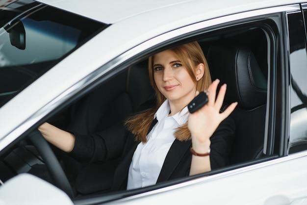 Jovem linda mulher de negócios sentada no carro