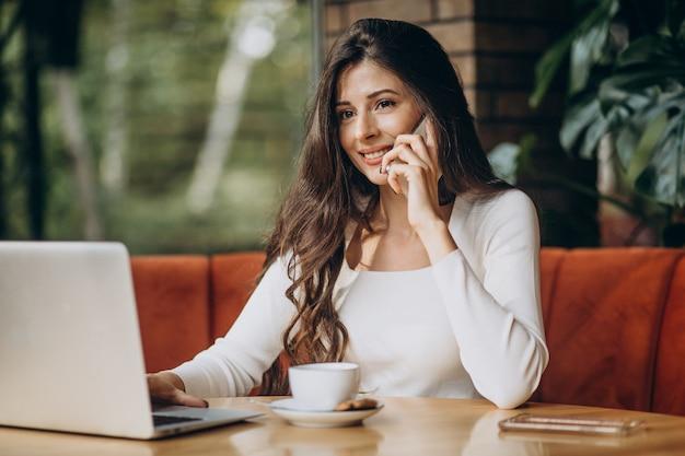 Jovem linda mulher de negócios trabalhando no computador em um café