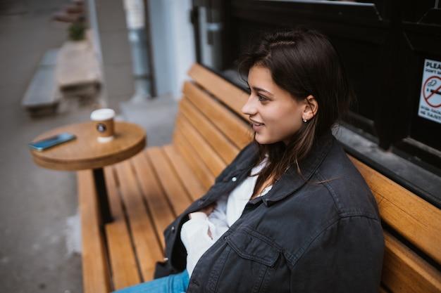 Jovem, linda mulher elegante, sentada no banco da rua, viajando sozinha, aproveite seu tempo livre