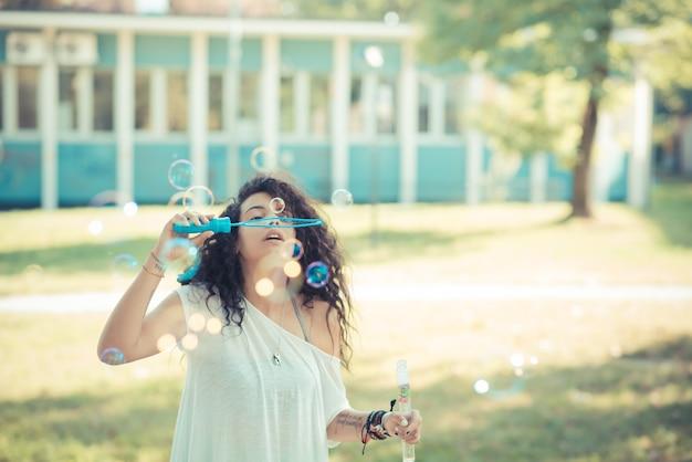 Jovem linda mulher encaracolada marroquina soprando bolhas