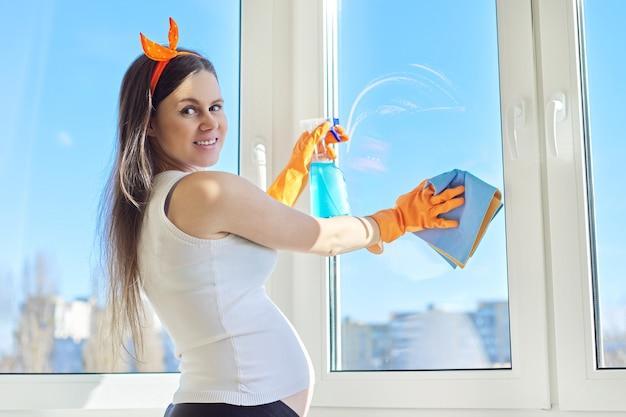 Jovem linda mulher grávida em luvas com pano de detergente, fazendo a limpeza doméstica. mulher no último mês de gravidez lavando janelas no quarto