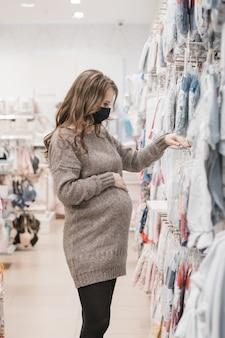 Jovem linda mulher grávida em máscara higiênica, escolhendo roupas de bebê para o recém-nascido.