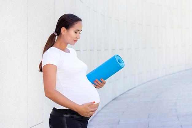 Jovem linda mulher grávida em uma camiseta branca está envolvida na aptidão. segura um tapete de ioga e esportes e mostra como