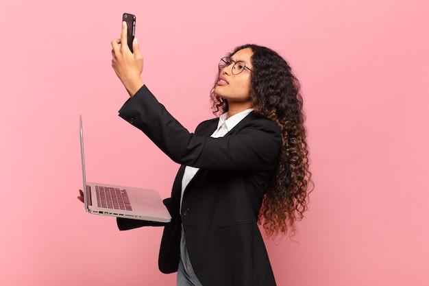 Jovem, linda mulher hispânica com laptop e smartphone