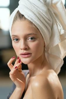 Jovem, linda mulher satisfeita em um pijama cinza de seda, aplicando o produto cosmético no rosto e desfrutando de manhã após o banho