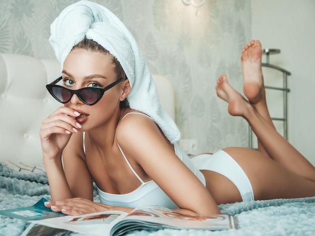 Jovem linda mulher sorridente em lingerie branca e toalha na cabeça