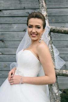 Jovem linda noiva em pé na escada no fundo da parede de madeira