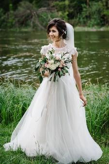 Jovem linda noiva em um vestido elegante está em pé perto do lago e segurando um buquê