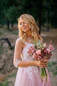 Jovem linda noiva segurando um buquê de casamento e sorrindo para o fundo da natureza