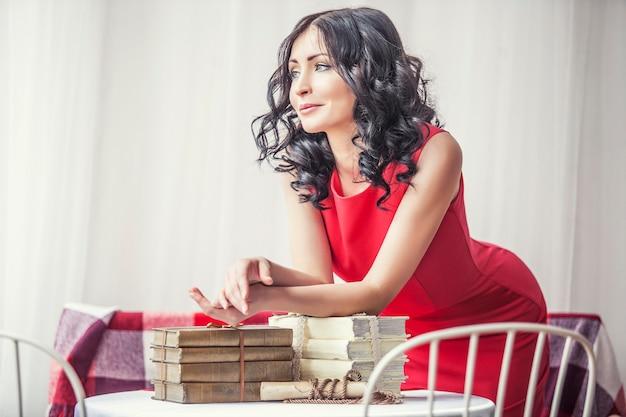Jovem linda num vestido vermelho com livros na mesa, olhando pela janela
