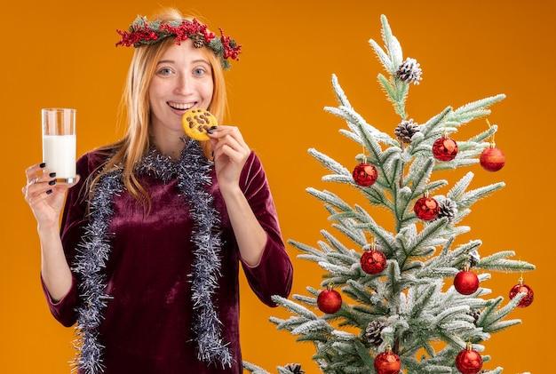 Jovem linda sorridente em pé perto da árvore de natal com vestido vermelho e grinalda com guirlanda no pescoço segurando um copo de leite e experimentando biscoitos isolados em fundo laranja