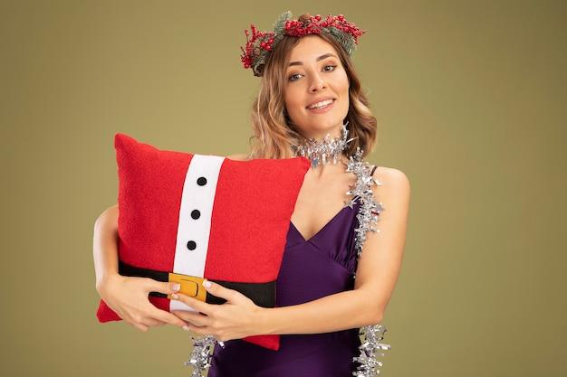 Jovem linda sorridente usando vestido roxo e grinalda com guirlanda no pescoço abraçava a almofada de natal isolada em fundo verde oliva