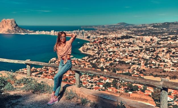 Jovem linda turista em óculos de sol, vestida de jeans e uma camisa está de pé perto de uma cerca de madeira no topo de um penhasco, por uma cidade costeira.