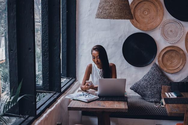 Jovem linda usa um laptop no café, navegar na internet