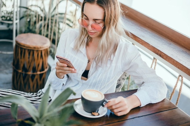 Jovem linda usa um smartphone na rua, navegar na internet