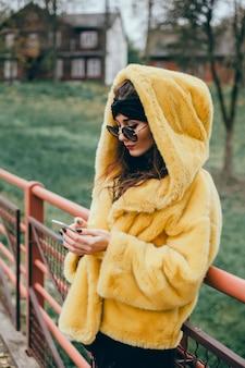 Jovem linda usa um smartphone na rua, surfando na internet e bebendo café