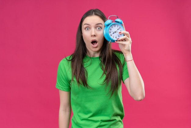 Jovem linda vestindo uma camiseta verde segurando um despertador parecendo espantada e surpresa em pé sobre um fundo rosa isolado