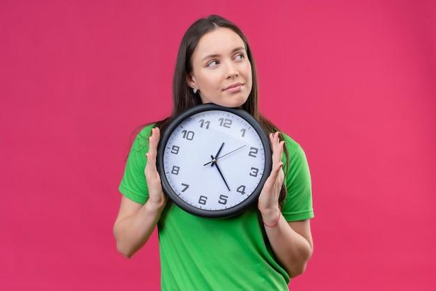 Jovem linda vestindo uma camiseta verde segurando um relógio olhando para o lado com um olhar sonhador sorrindo em pé sobre um fundo rosa