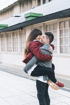 Jovem lindo casal apaixonado, abraçando-se no meio da rua de uma maneira romântica