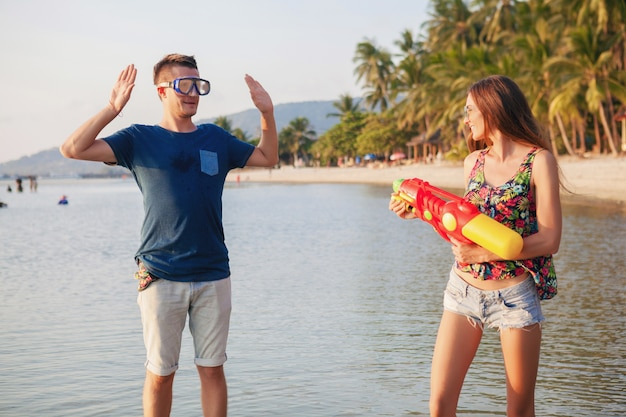 Jovem lindo casal apaixonado brincando em uma praia tropical, férias de verão, lua de mel, romance, pôr do sol, feliz, se divertindo, pistola d'água, briga, homem desiste, positivo, engraçado