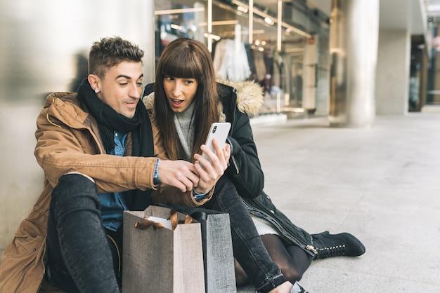 Jovem lindo casal apaixonado, fazer compras na rua, fazendo uma pausa no chão, fazer compras no celular