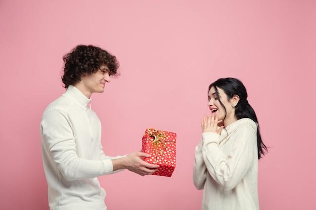 Jovem lindo casal apaixonado na parede rosa do estúdio Foto gratuita