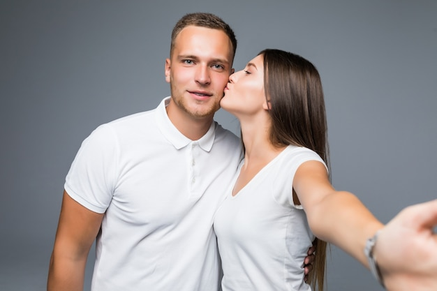 Jovem lindo casal apaixonado tirando foto de selfie romântico de auto-retrato junto com o celular sorrindo feliz vestindo roupas da moda isoladas no fundo cinza