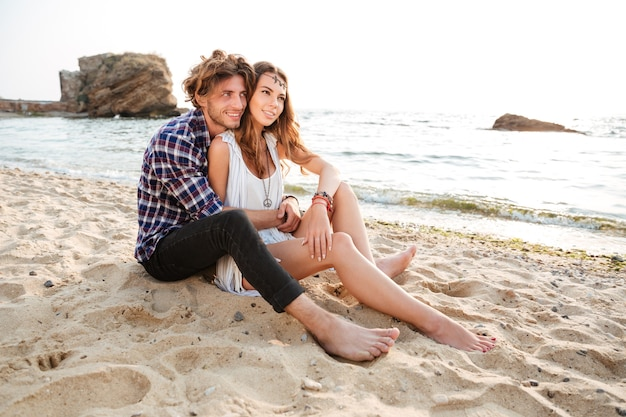 Jovem lindo casal feliz apaixonado se abraçando enquanto está sentado na praia