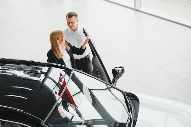 Jovem lindo casal feliz comprando um carro. marido comprando carro para sua esposa em um salão. conceito de compra de carro.