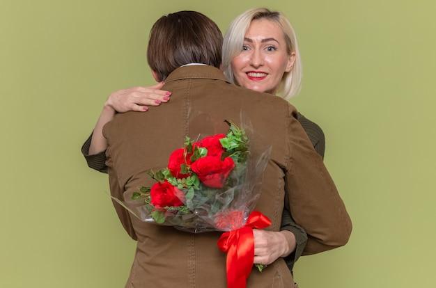 Jovem lindo casal feliz, homem e mulher com buquê de flores, abraçando, felizes e apaixonados, sorrindo, celebrando o dia internacional da mulher em pé sobre a parede verde