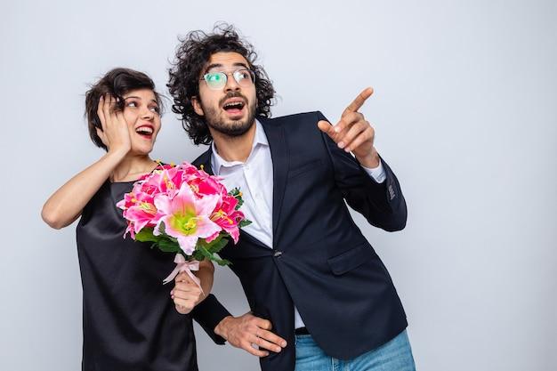 Jovem lindo casal feliz, homem e mulher com buquê de flores, olhando de lado feliz e surpreso, apontando com o dedo indicador para o lado, comemorando o dia internacional da mulher, 8 de março.