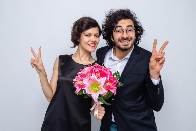 Jovem lindo casal feliz, homem e mulher com buquê de flores, olhando para a câmera, sorrindo alegremente mostrando os polegares para cima, celebrando o dia internacional da mulher, 8 de março, em pé sobre um fundo branco