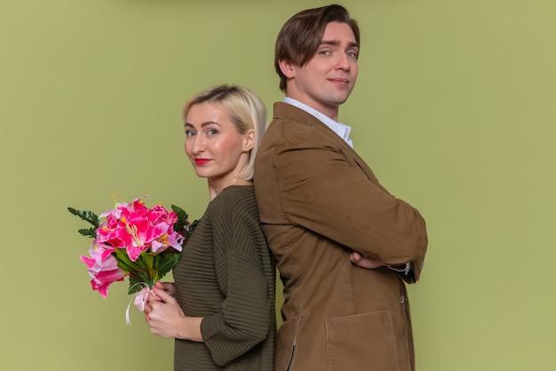Jovem lindo casal feliz, homem e mulher com buquê de flores, olhando para a frente, sorrindo, confiante, comemorando o dia internacional da mulher, em pé, costas com costas, sobre a parede verde