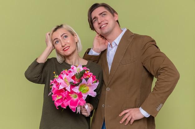 Jovem lindo casal feliz, homem e mulher com buquê de flores