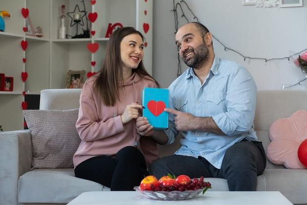 Jovem lindo casal feliz, homem e mulher com um livro, passando um tempo juntos, comemorando o dia internacional da mulher, sentado em um sofá em uma sala iluminada