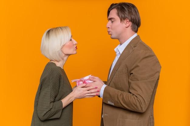 Jovem lindo casal feliz, homem e mulher com um presente feliz e apaixonado, celebrando o dia internacional da mulher em pé sobre a parede laranja
